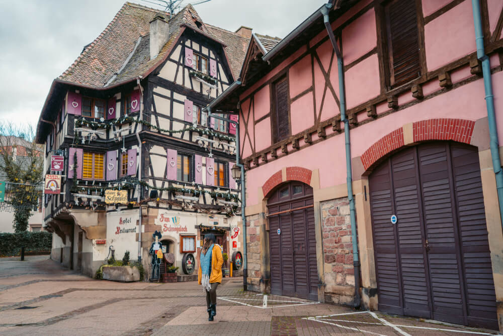 Travel blogger in yellow coat in front of a half timbered house with purple shutters in obernai