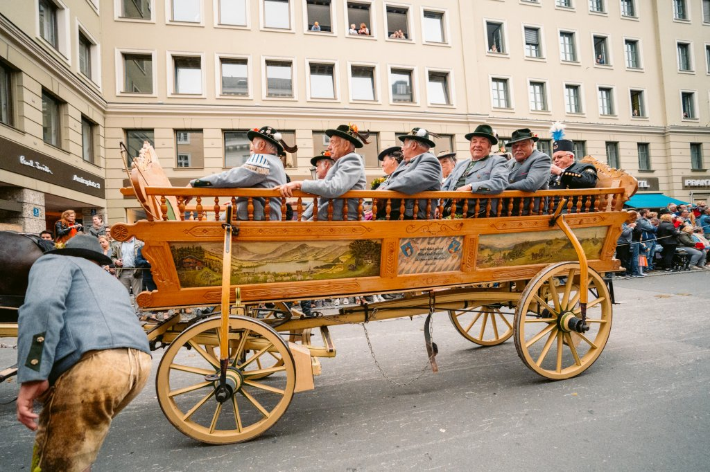 A cart full of Bavarian men in traditional clohes during the annual trachten parade in Munich, Germany