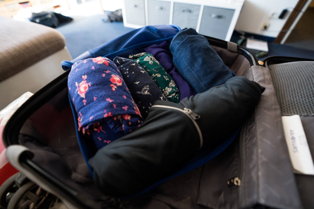 Rolled clothes in a packing cube inside a suitcase