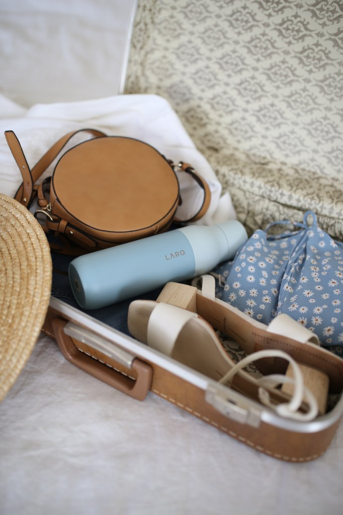 Open suitcase filled with pretty vacation picks like a floral dress, sandals and a hat