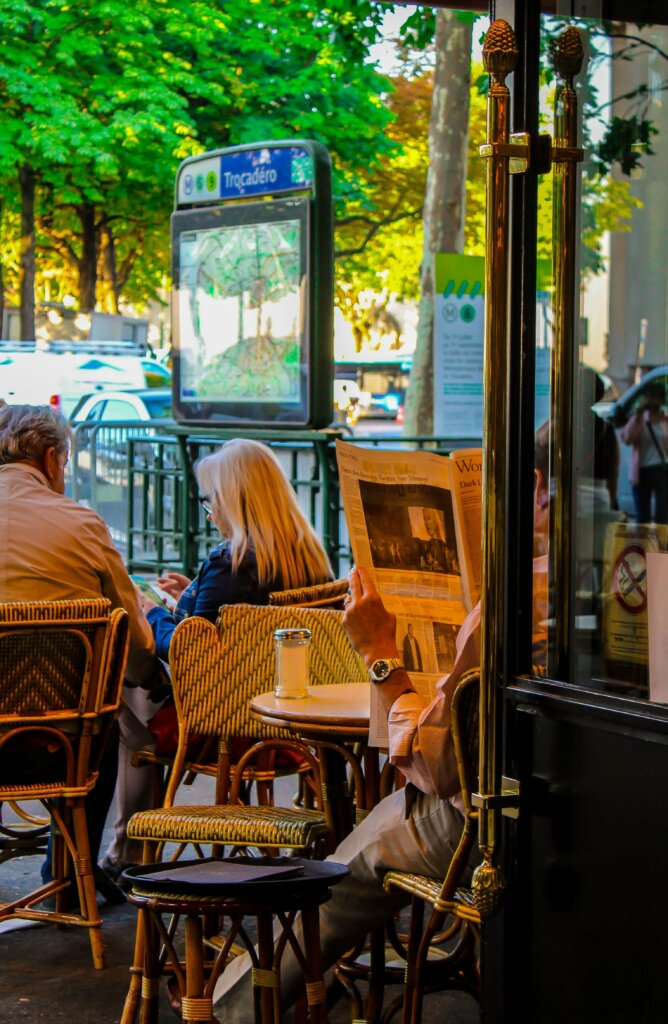 Man reading newspaper at Parisian cafe