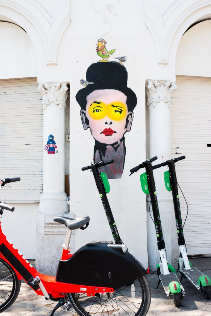Lime scooters in paris in front of a street mural