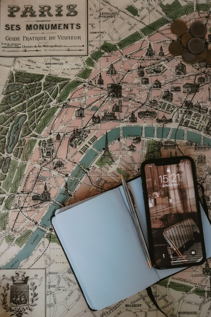 Tourist map of Paris with a notebook on top and a phone