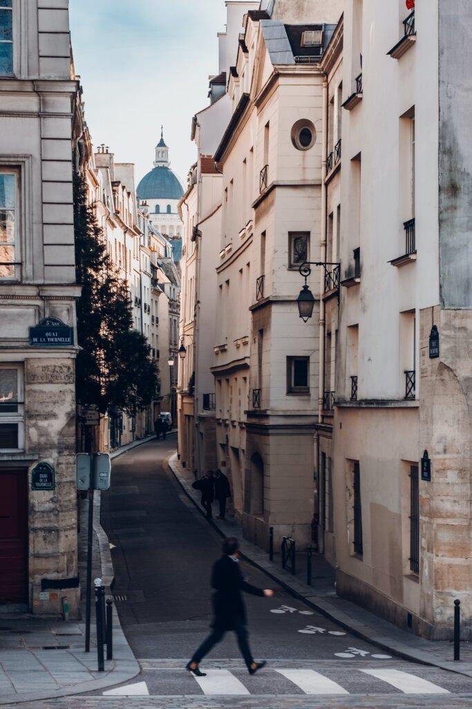 Man walking across the street in a narrow Parisian street