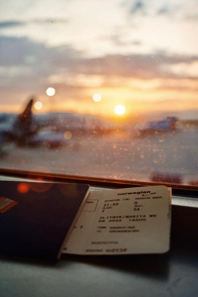 Plane ticket inside passport on a table at the airport at sunset