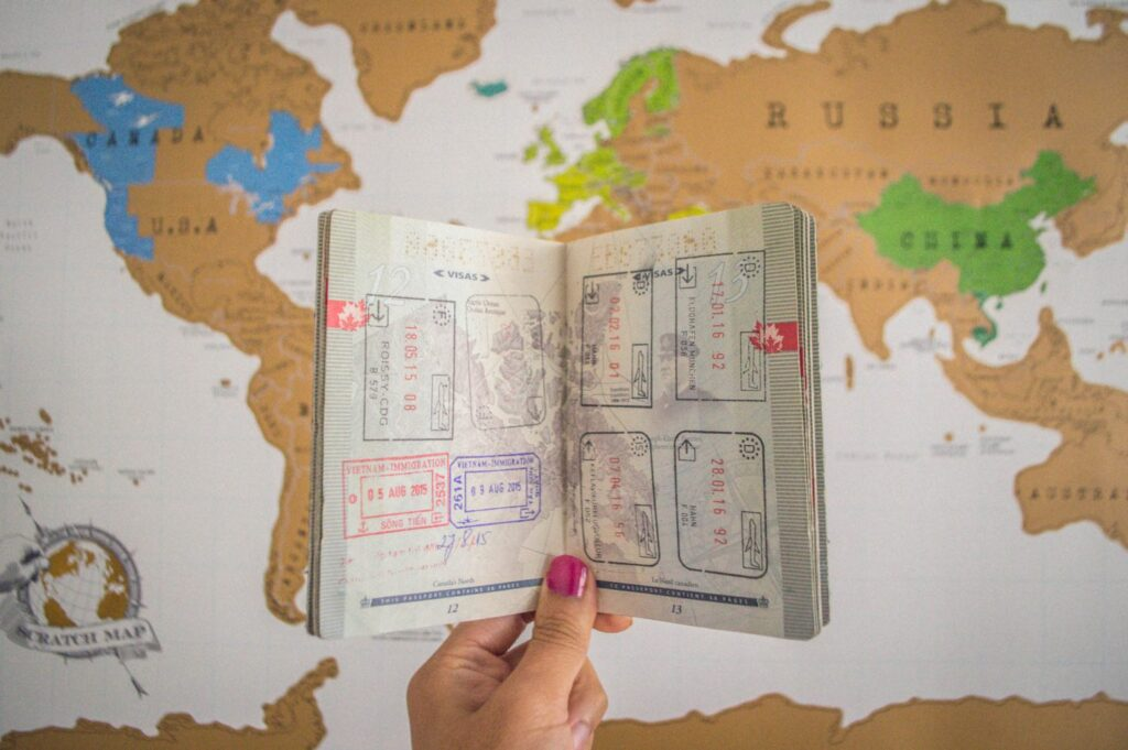 Passport being held out in front of a map