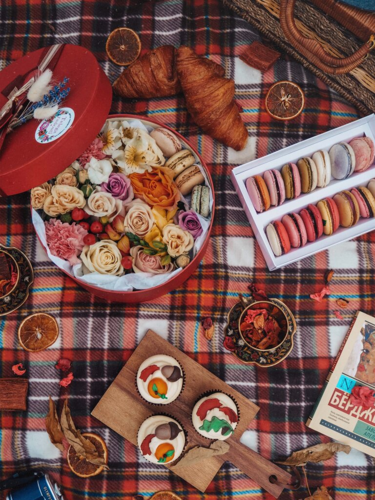 Picnic spread with cupcakes and a baguette on a checkered blanket