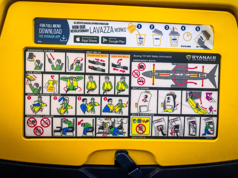 Back of RyanAir seat with safety instructions and an ad