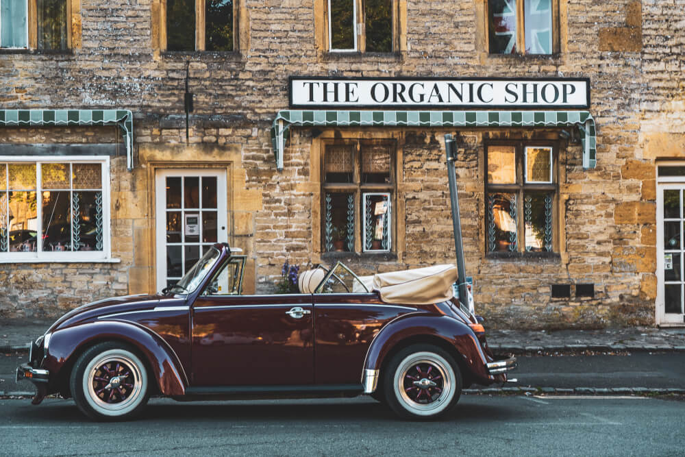 A cute vintage car parked in front of a shop in Stow in the Wold