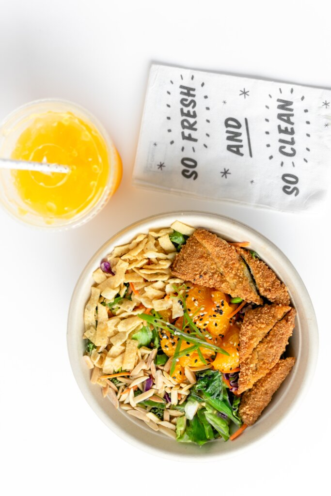 Takeout meal with orange juice on a white background