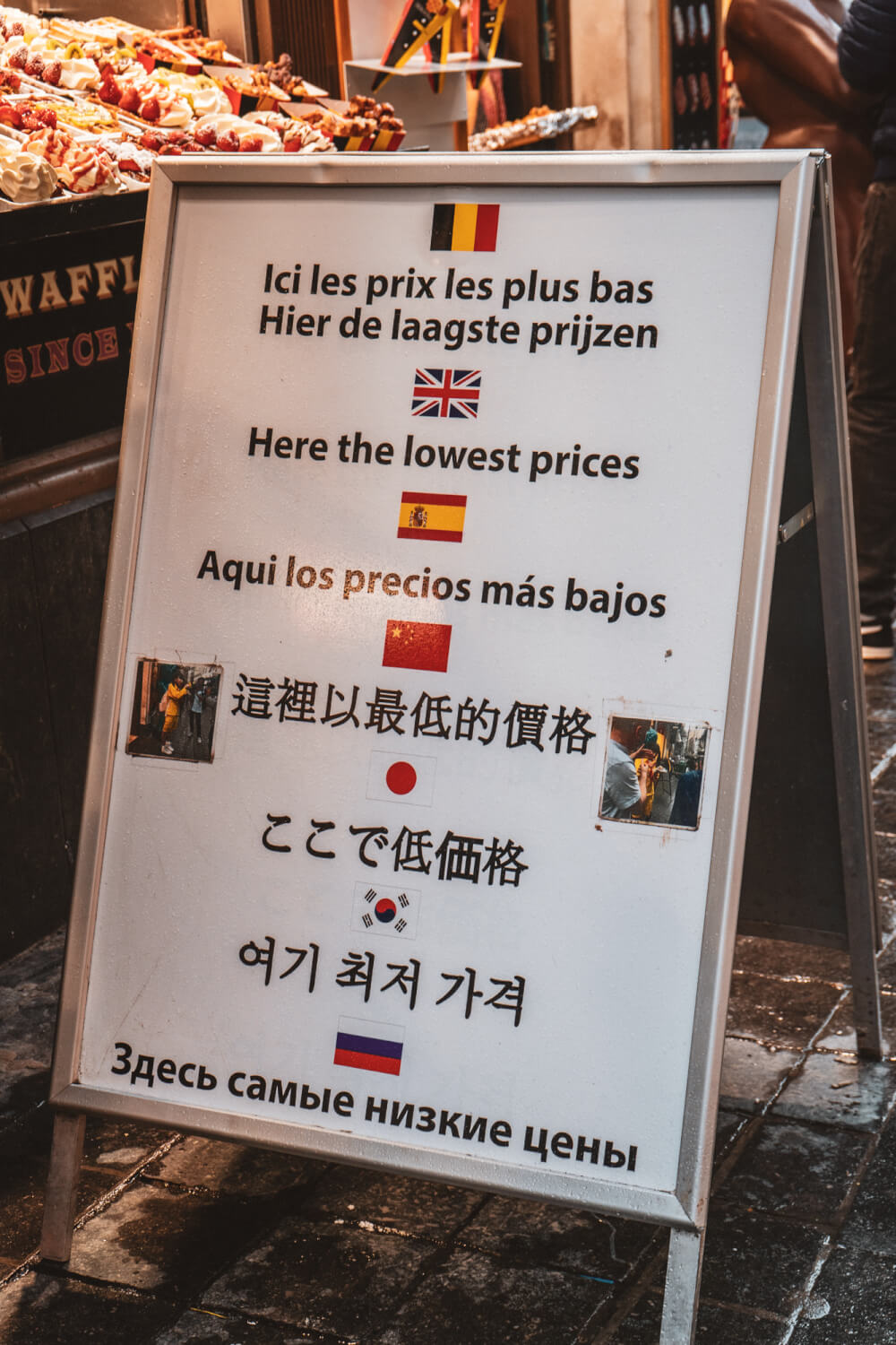 Sign in Brussels city center with multiple languages saying they have the cheapest prices for waffles