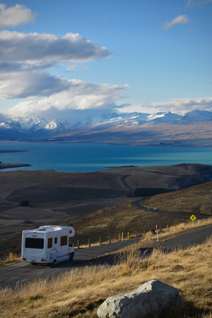Faraway shot of an RV driving on a scenic road