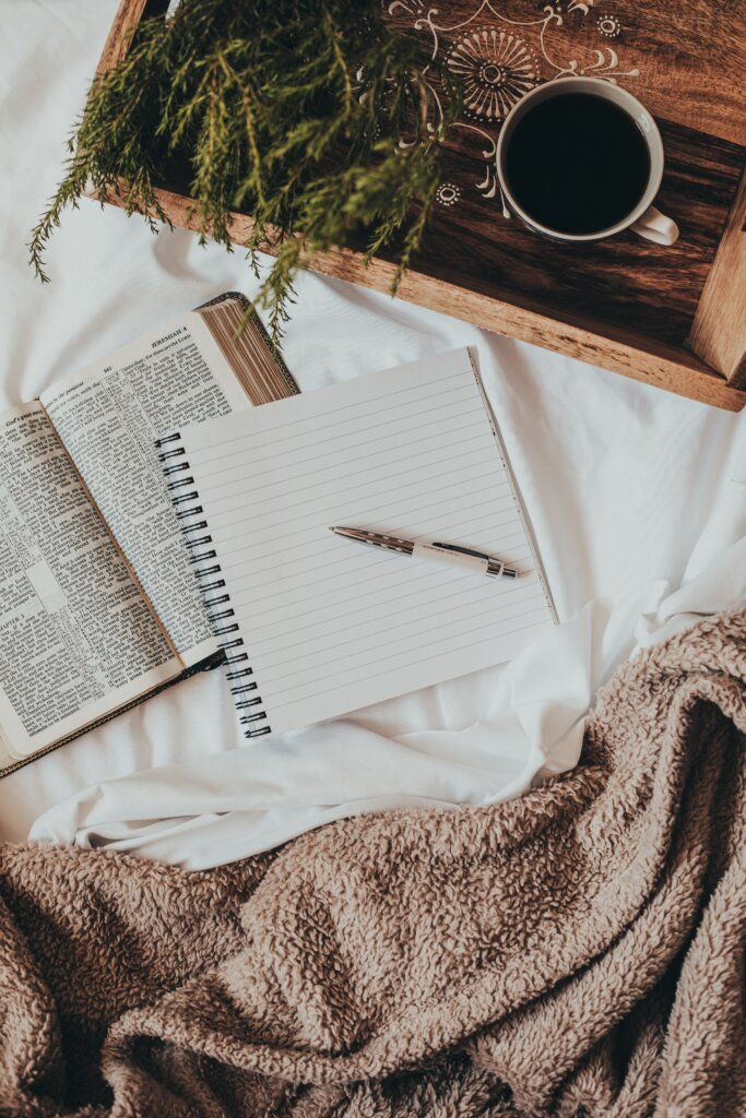Notebook on a bed with a book behind it and a cozy blanket