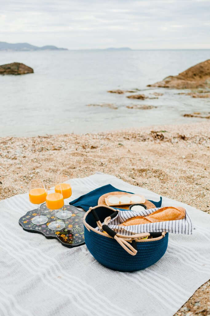 Beach picnic with a baguette and orange juice