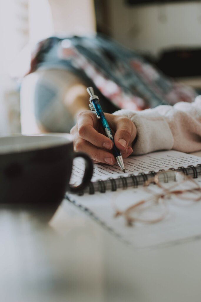 Woman writing in a notebook with a mug of coffee