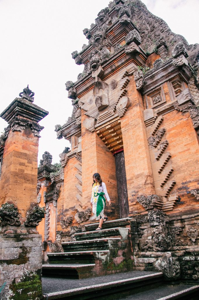 Girl in Balinese clothing walking down stairs at a Balinese temple