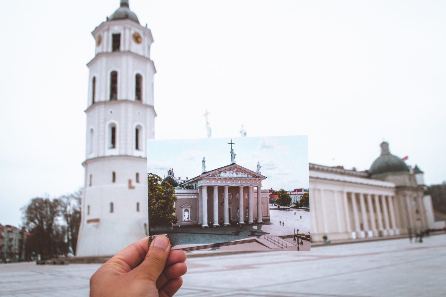 Postcard being held up in Cathedral Square in Vilnius, Lithuania