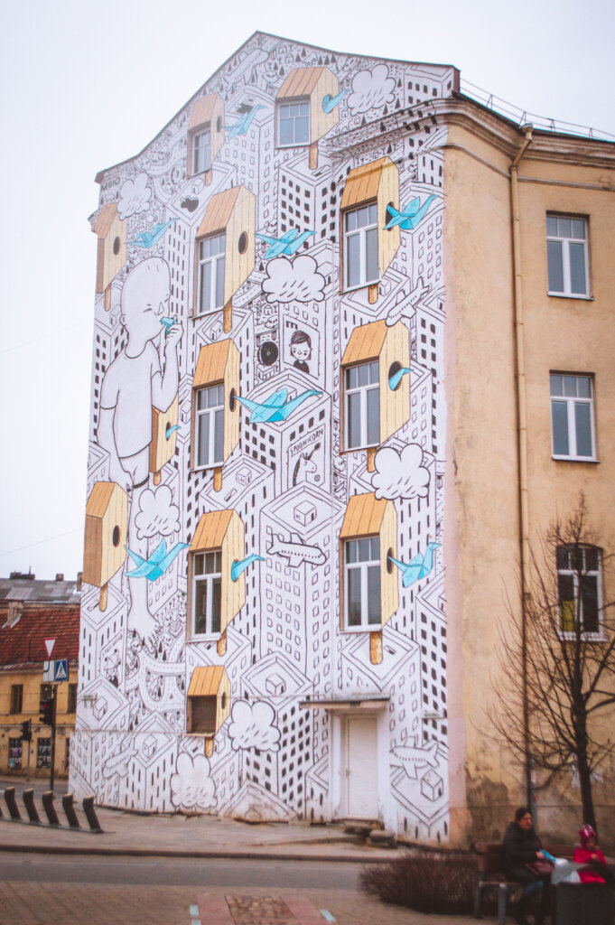 Large street art mural covering the whole side of a building in Vilnius, Lithuania