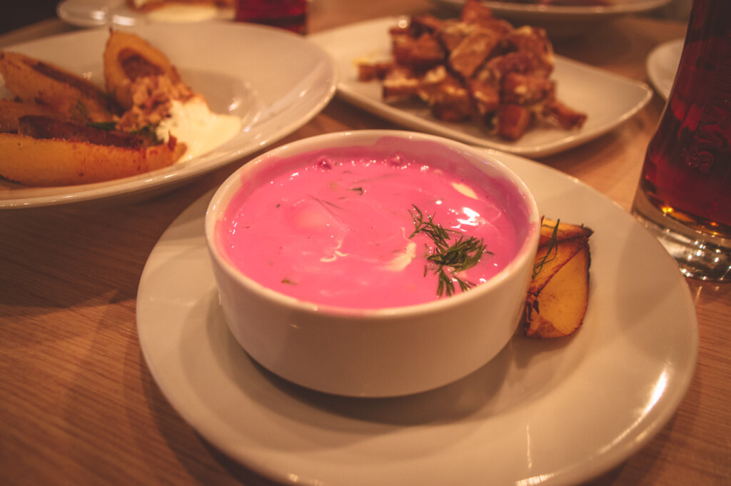 Cepelinai, a chilled beetroot soup in a bowl surrounded by other dishes