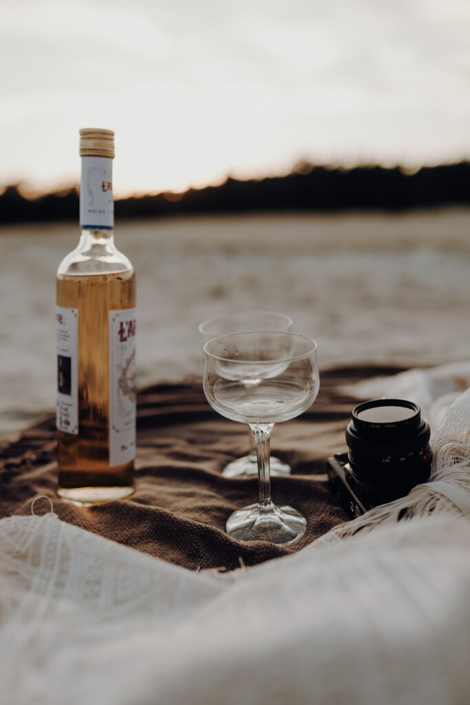 Wine glasses with wine on a beach with picnic blanket