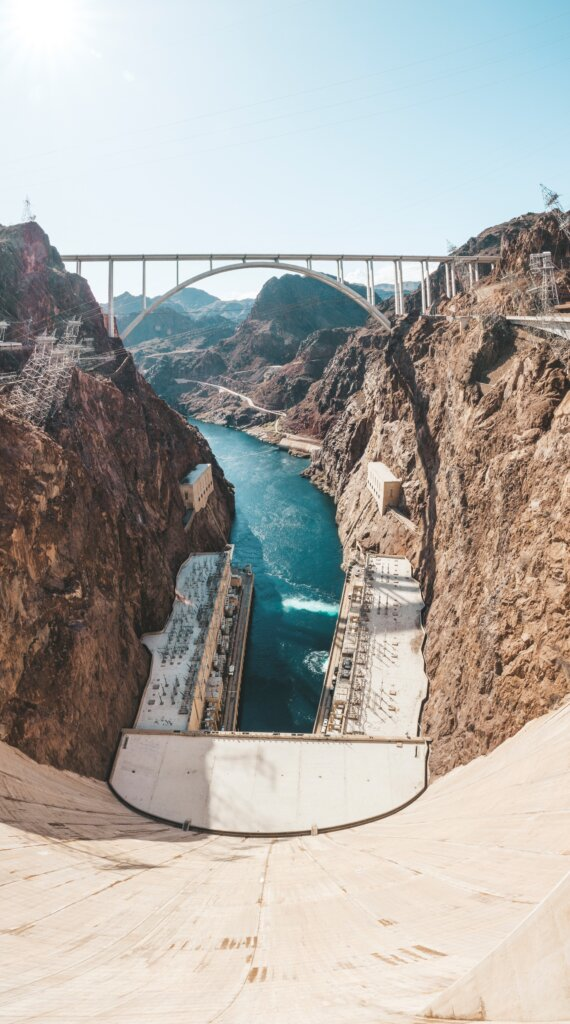 Looking down at the water from the top of hoover dam on a sunny day.