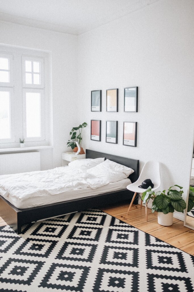 White bedroom with geometric rug and nice photos on the wall