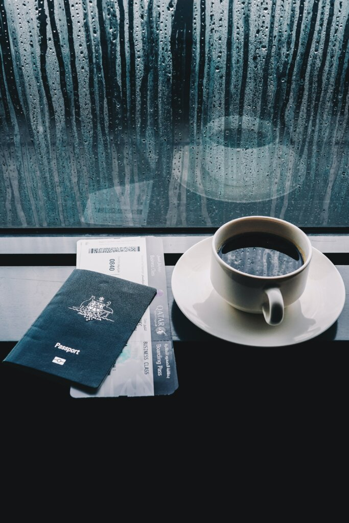 Passport and boarding pass with coffee at airport