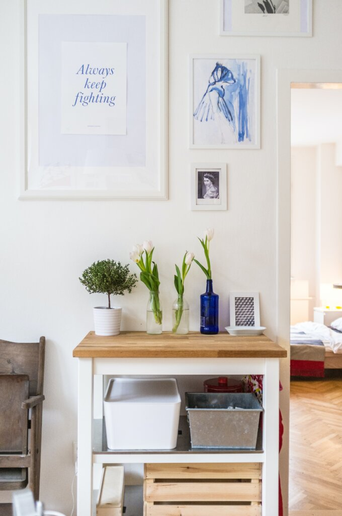 A clean and airy living space with plants and photos on the wall