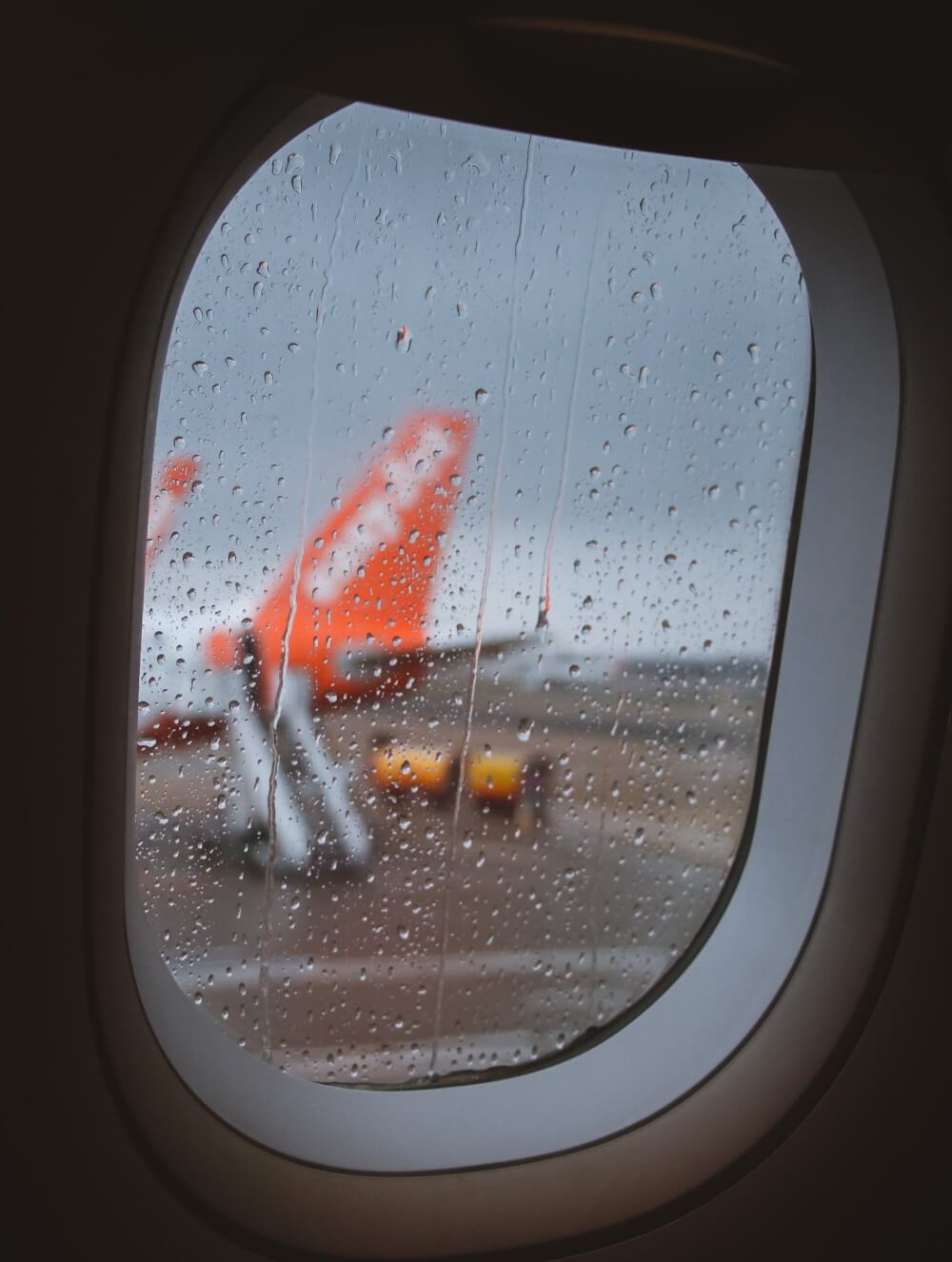 Rainy plane window looking out onto another plane