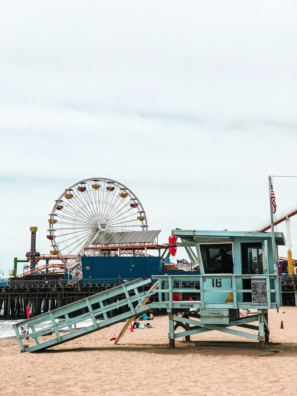 The pacific pier, with all its rides, the Ferris Wheel, and people laying on the beach.