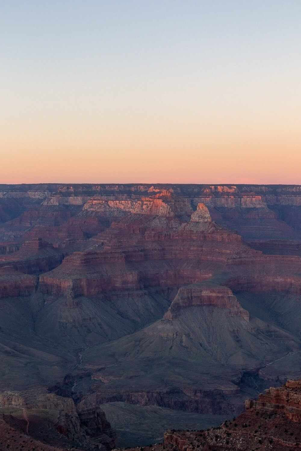 A view of the grand canyon at dusk, showing the various layers of rock.
