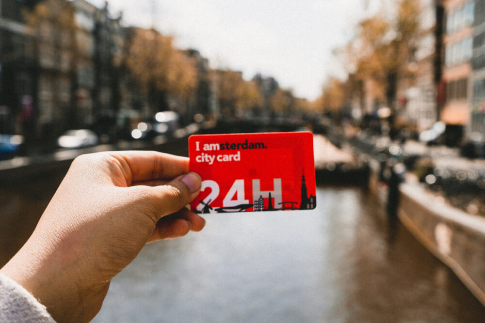Amsterdam card being held up over a canal