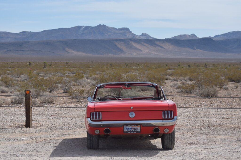 A red car parked in front of an arid, desert expanse of land.