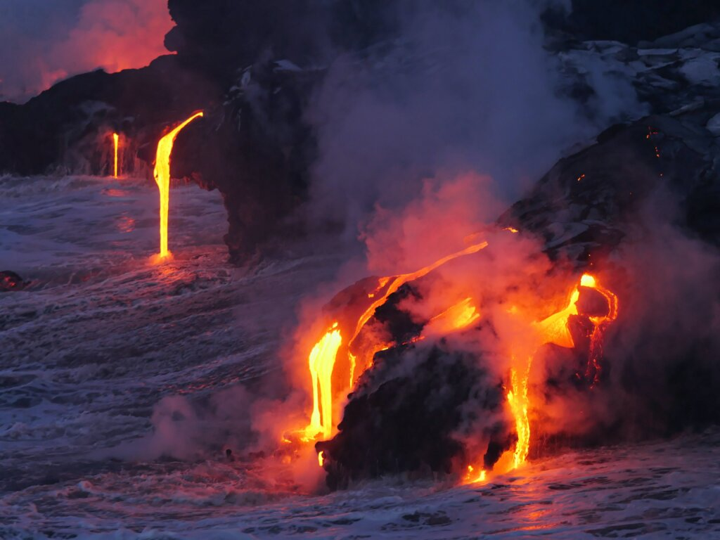 Molted lava running into the ocean at dusk.