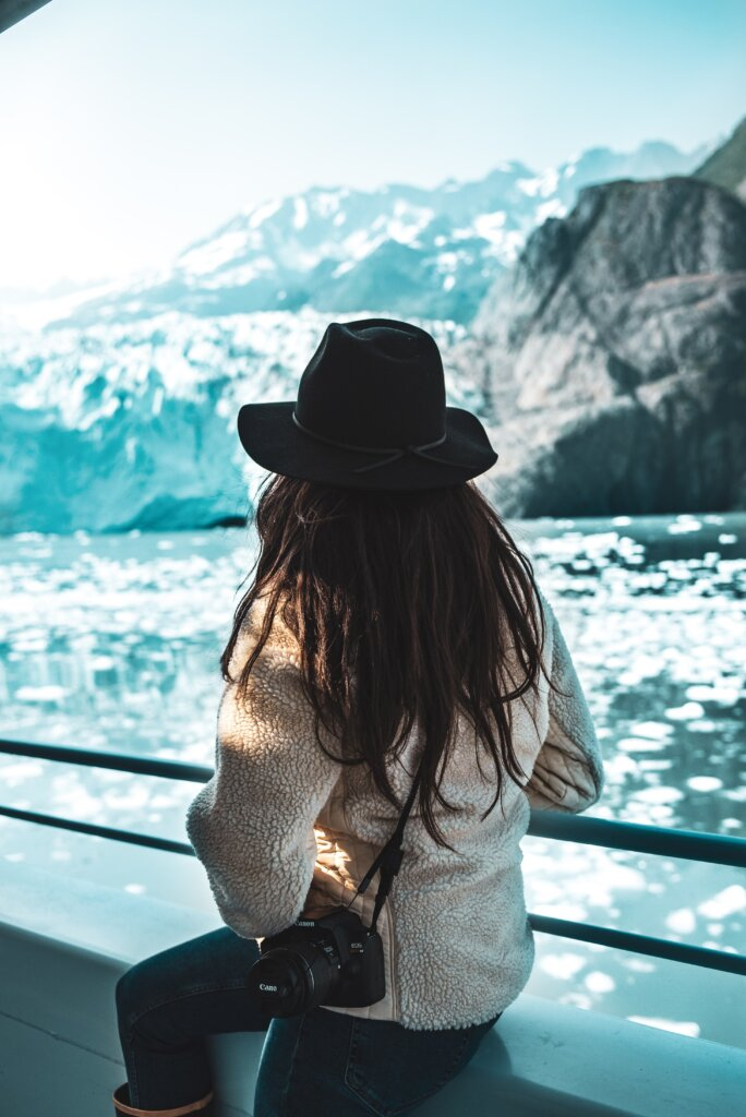 A woman with a hat on a ferry in Alaska, marveling at a glacier.