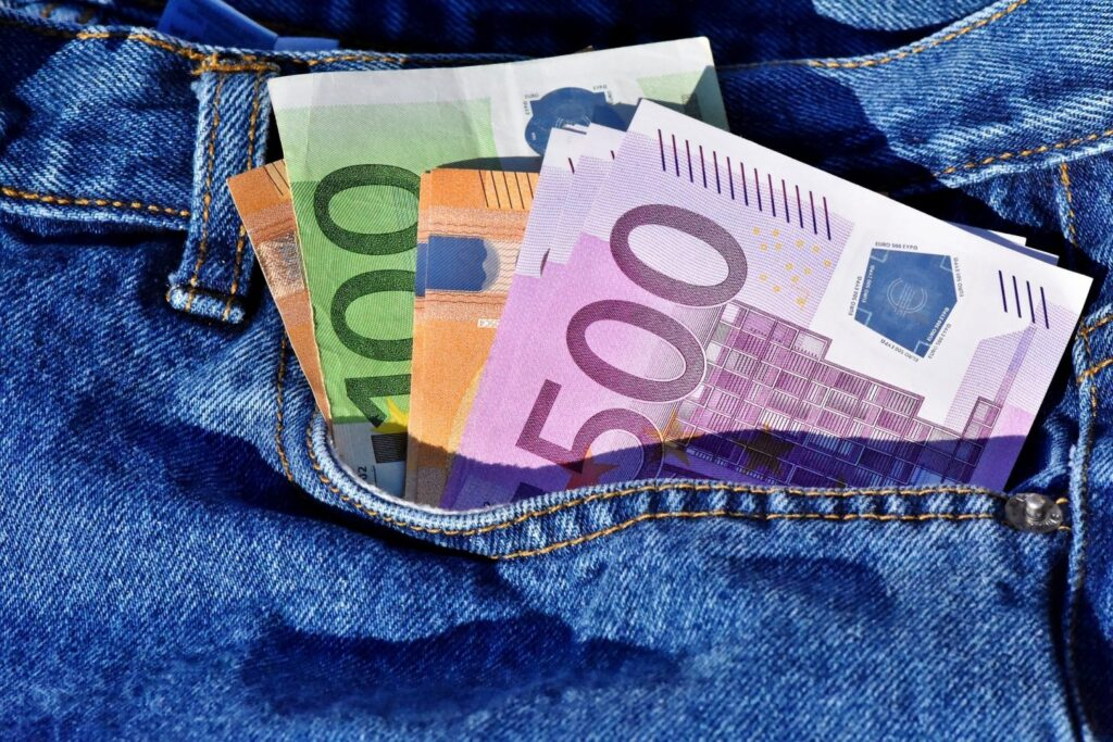 Euro bills sticking out of a jean pocket