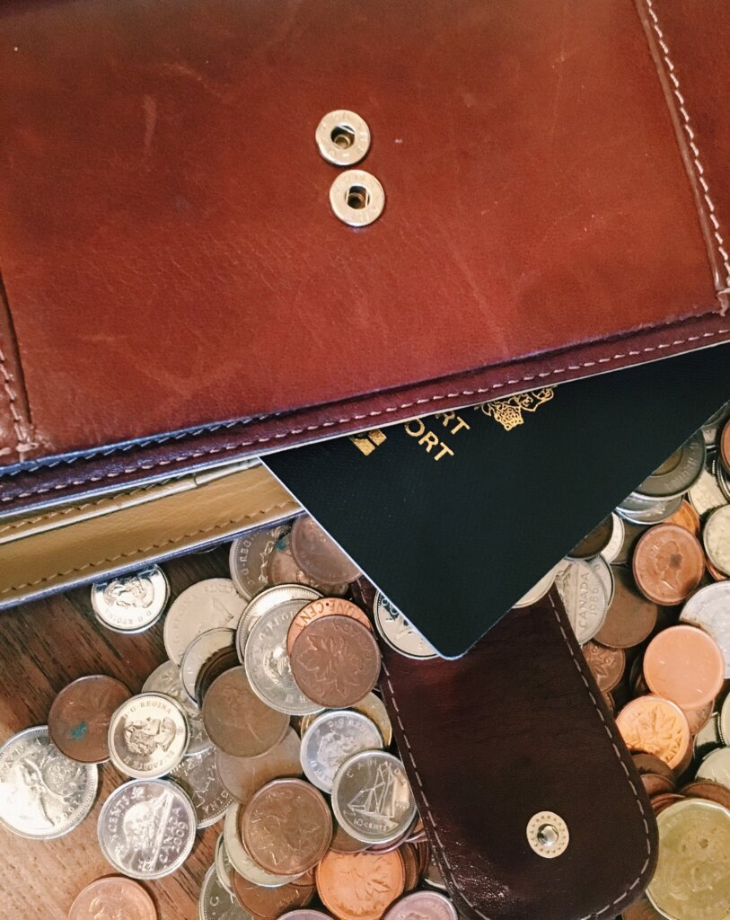 Wallet and passport on top of a pile of coins