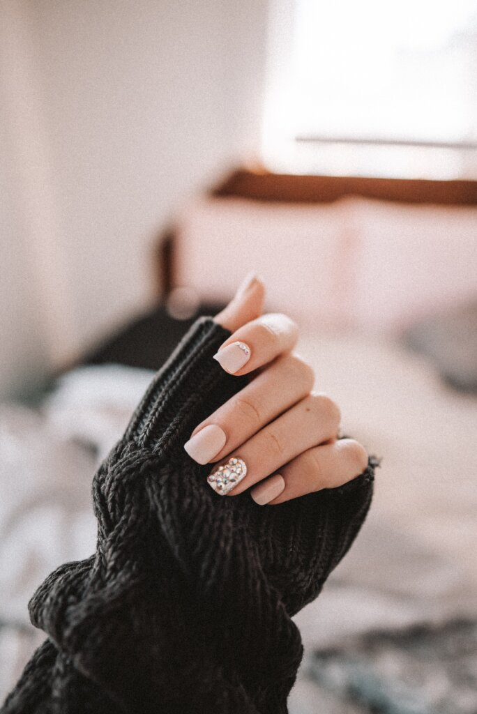 A person wearing a black sweater showing off their nails