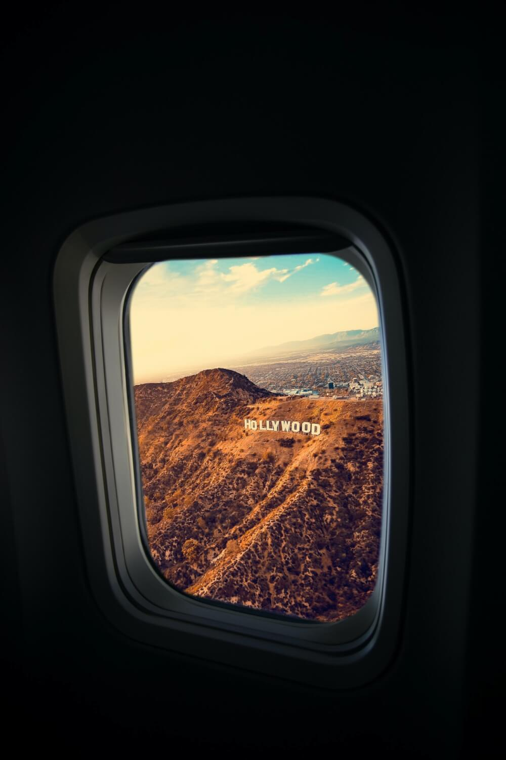 A view of the Hollywood sign from the airplane, positioned on a brown, arid hillside that's sparsely vegetated.