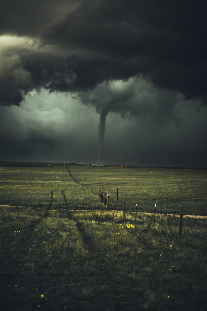 A tornado touching down in the distance, connecting earth to sky.