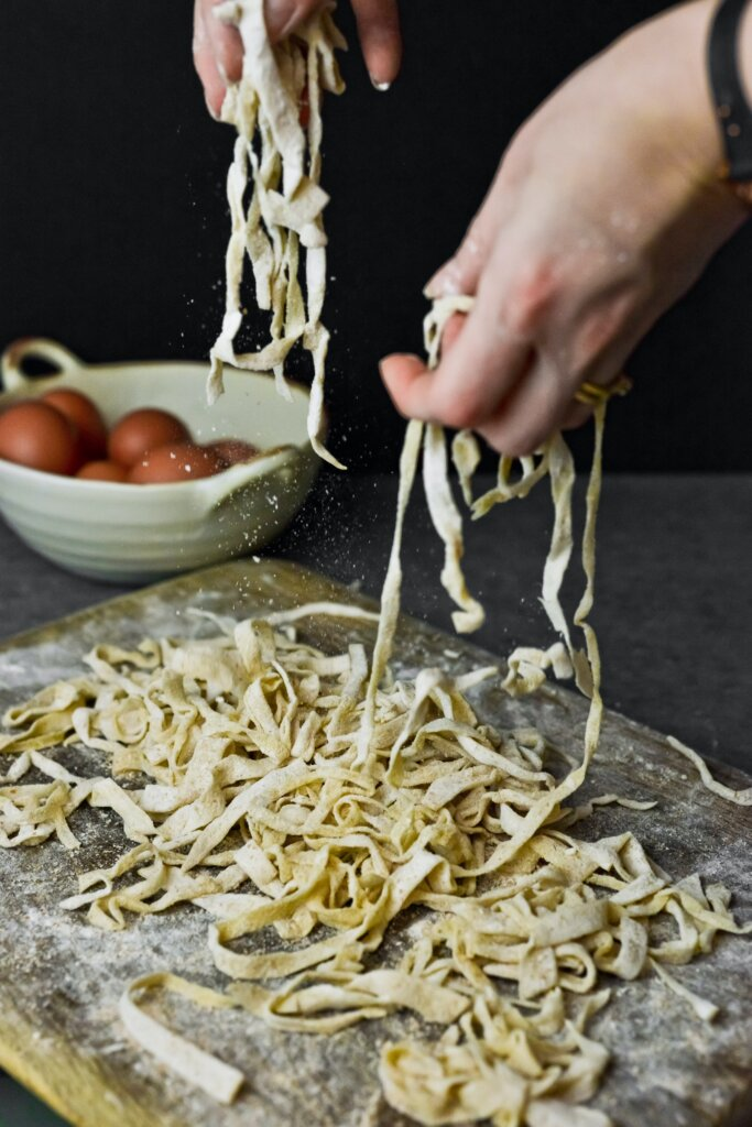 Raw pasta being made on a floured table