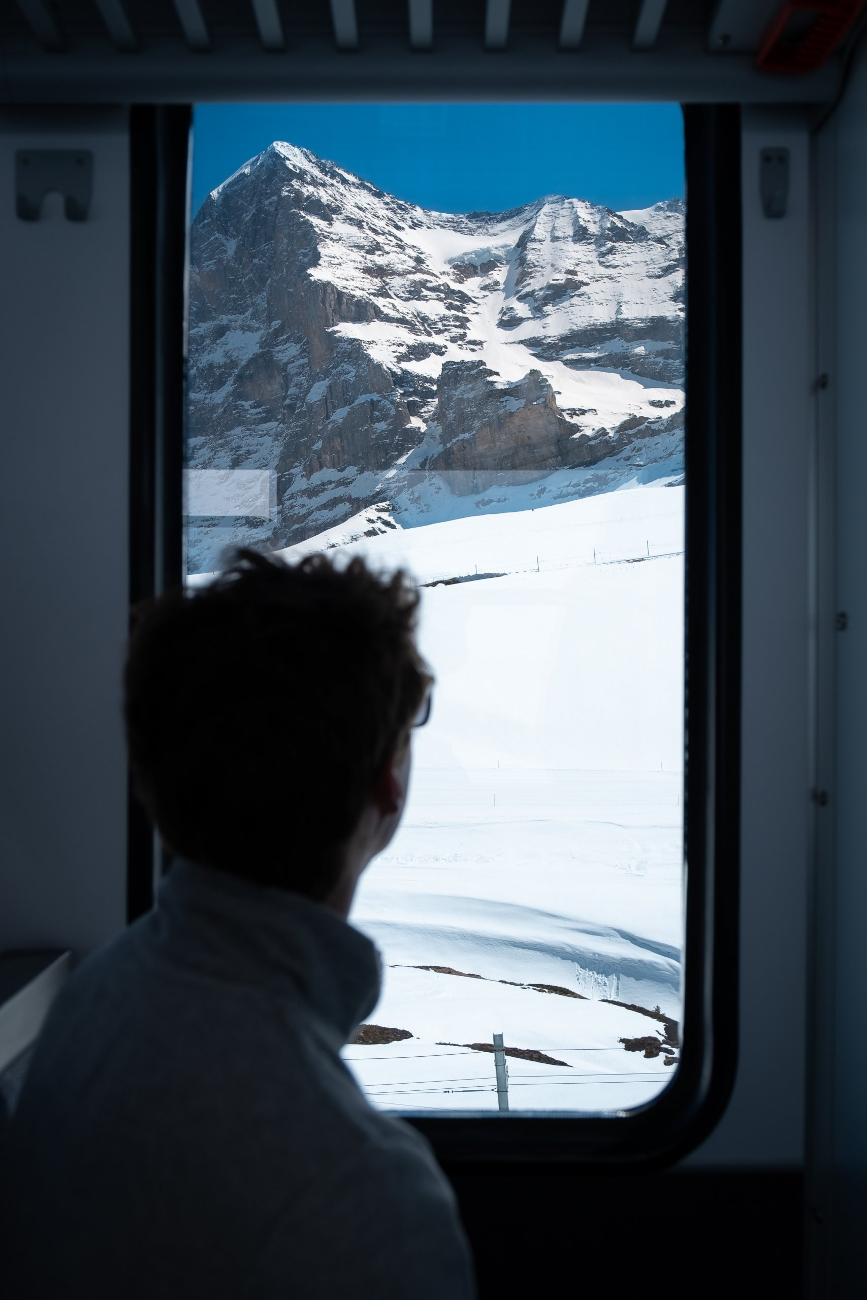 Passenger looking out window on a Swiss train