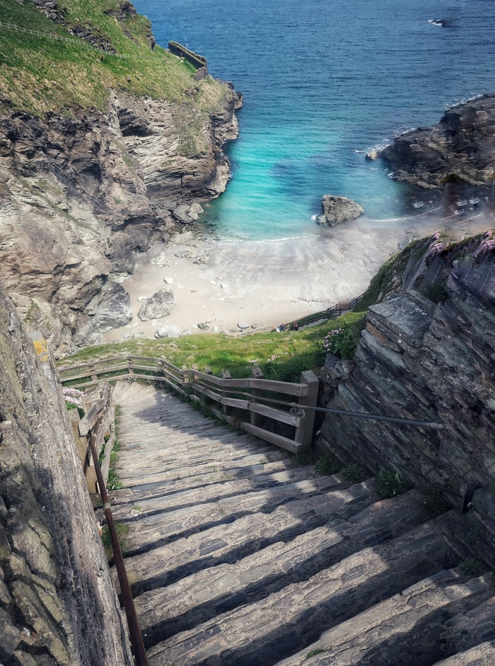 A steep walkway leading down to a turquoise water beach in Cornwall, England.