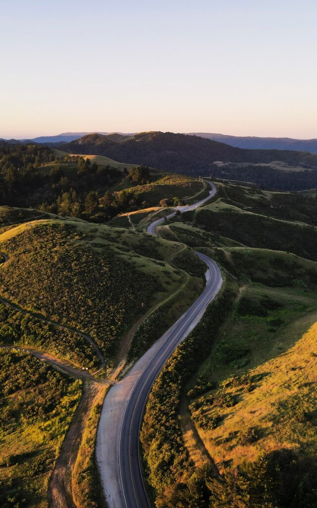 Winding road at sunset among green hills