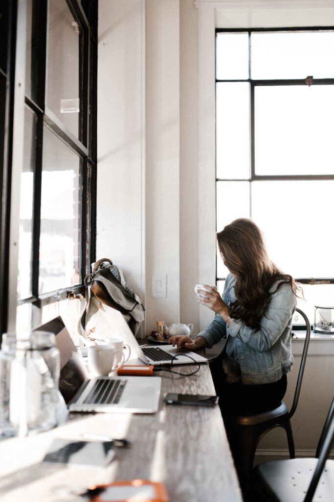 Girl at desk shopping online with a coffee in hand