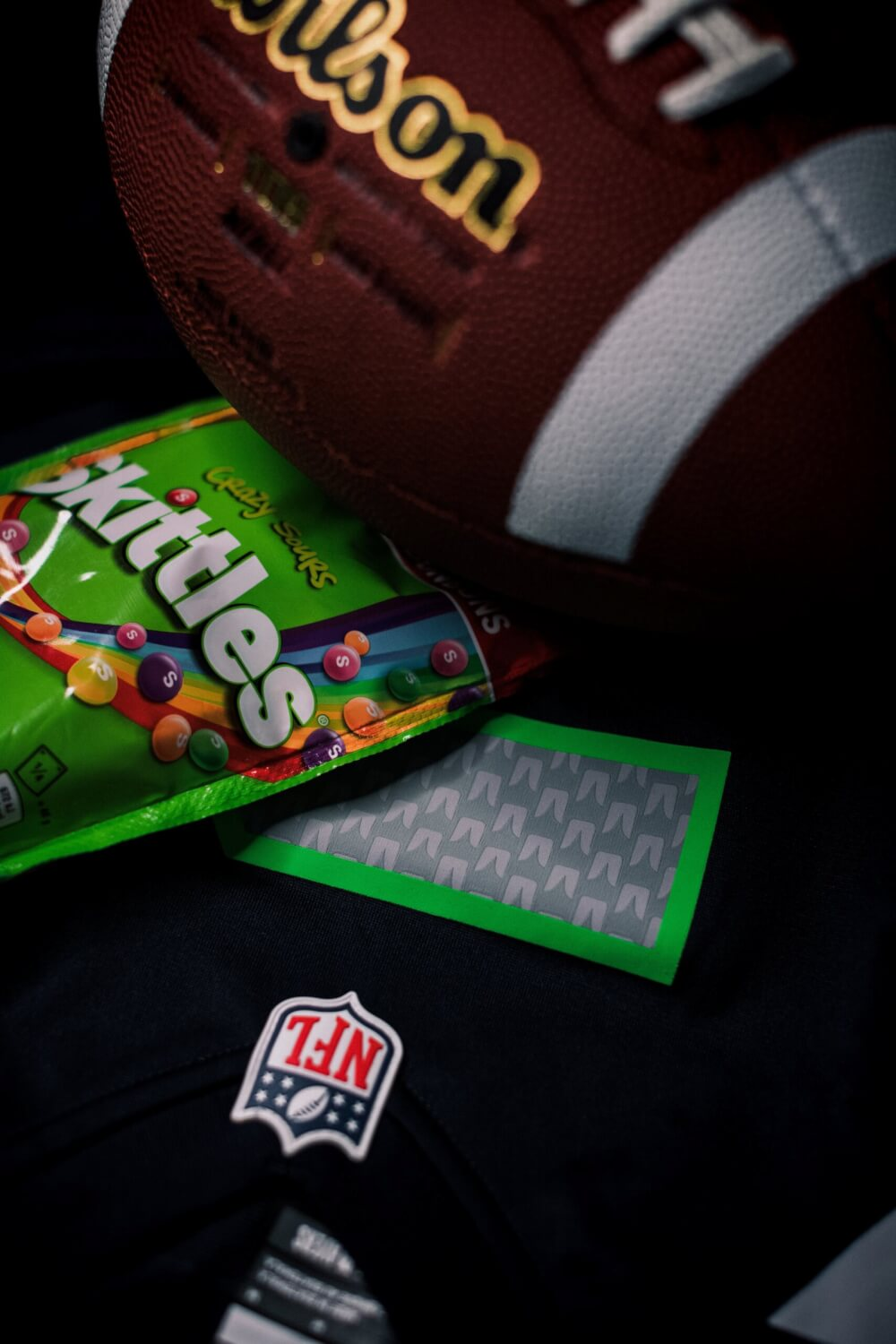 A Seattle Seahawks jersey and football. A pack of skittles is on top, which happens to be what fans would often see Marshawn Lynch eat on the sidelines.