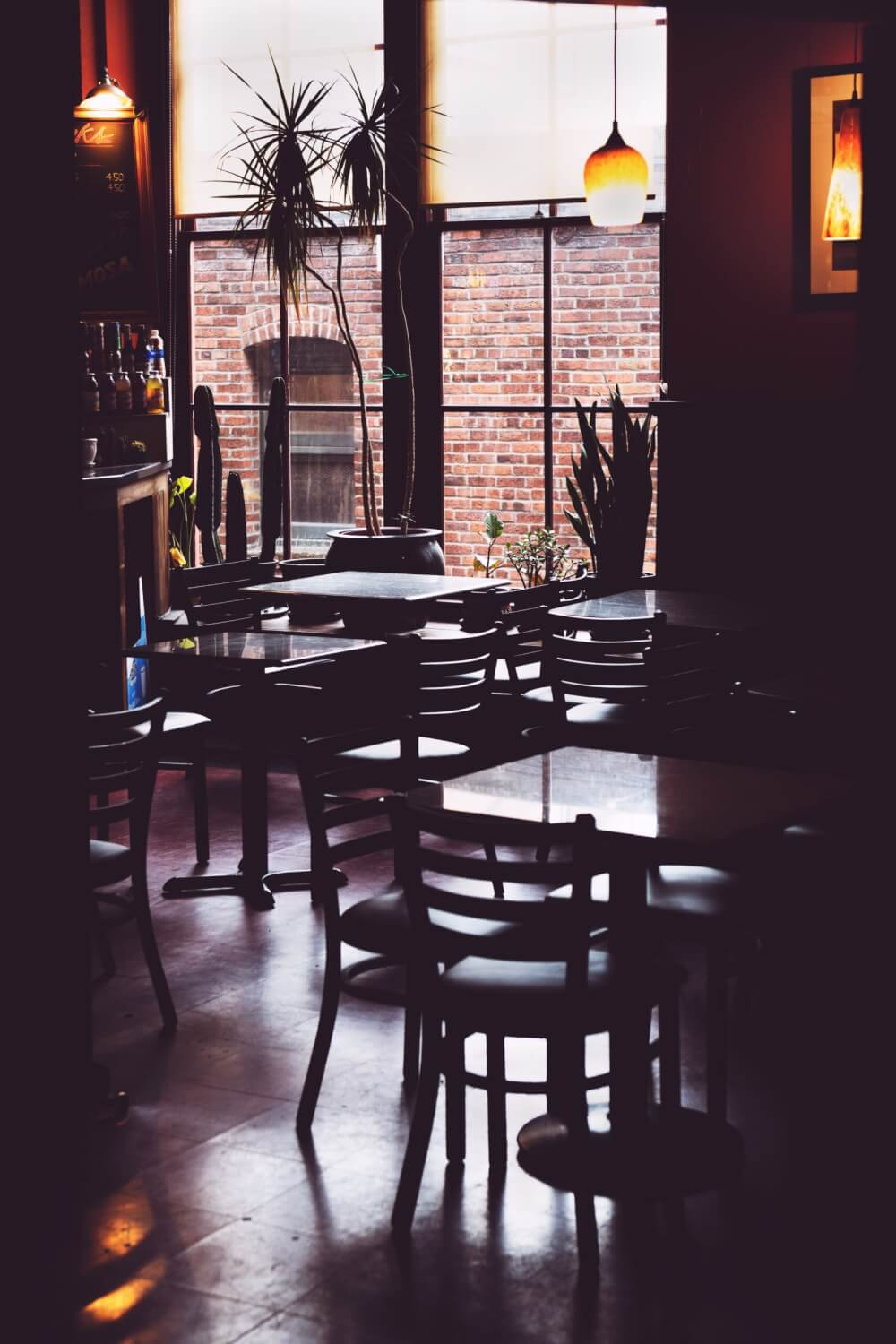 A view of an empty cafe, with a brick wall outside its window and the lights turned off.