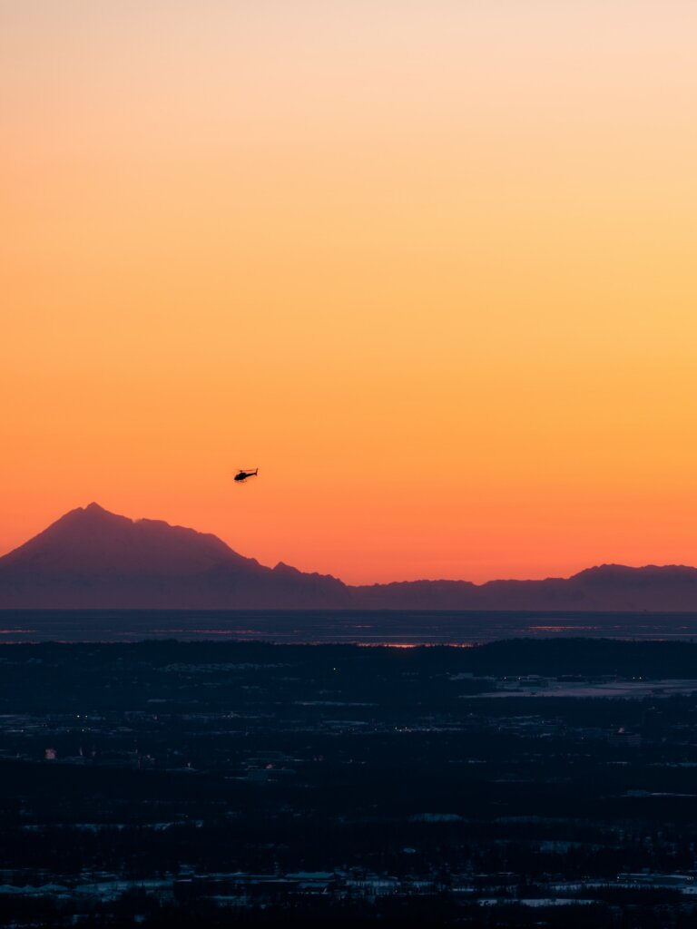 A view of a helicopter  flying over a mountain range, superimposed over a lurid sky.