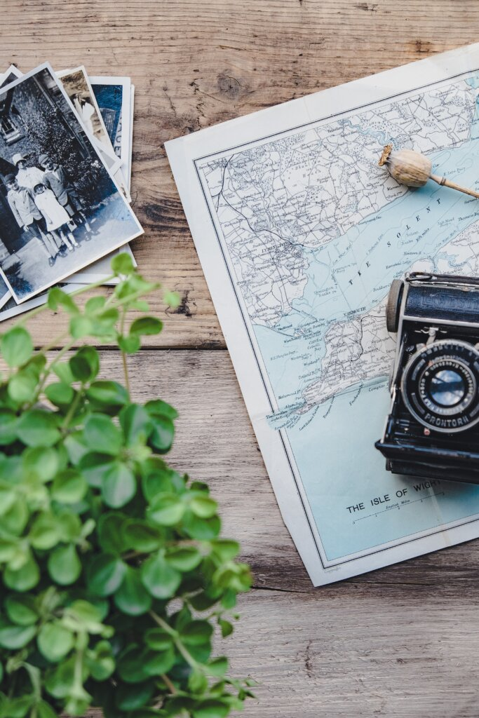 Photos and camera on top of a map on a wooden table