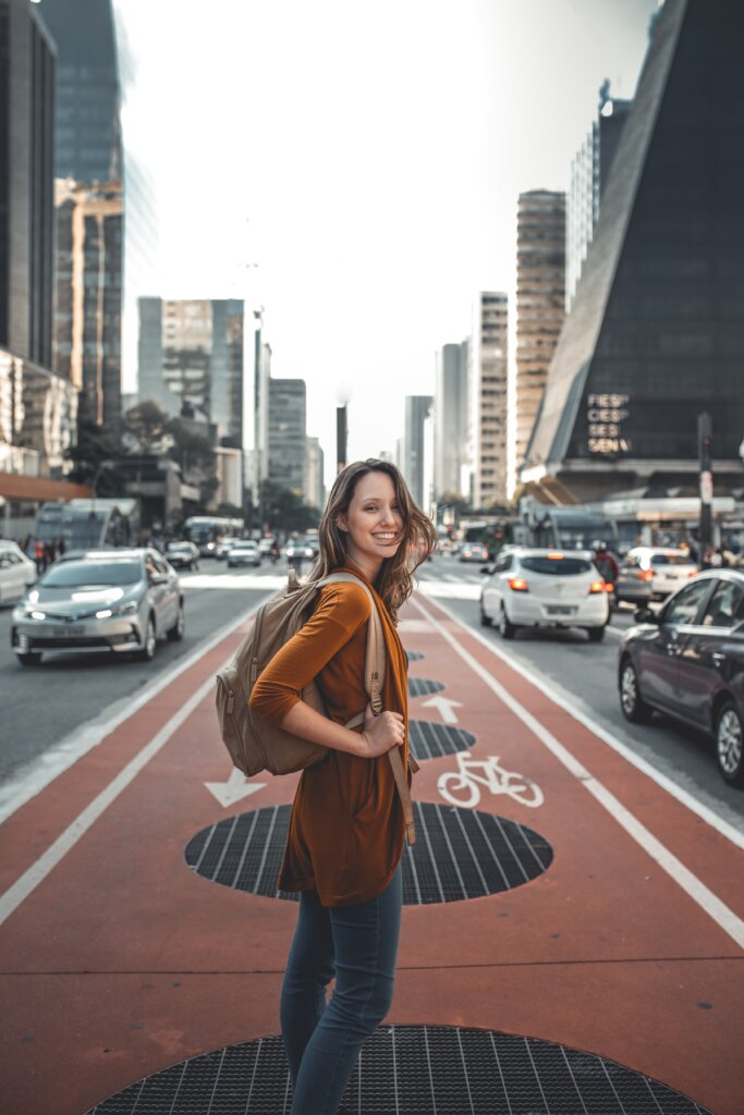 Woman with a backpack smiling on a road while crossing